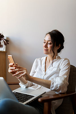 Smiling woman using mobile phone while sitting with laptop on chair at home - p300m2276656 by Valentina Barreto