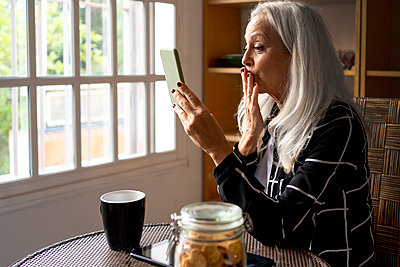 Senior woman blowing kiss during video call through smart phone at home - p300m2287554 by Eloisa Ramos