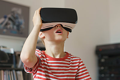 Boy wearing virtual reality simulator at home - p301m1148182 by Halfdark