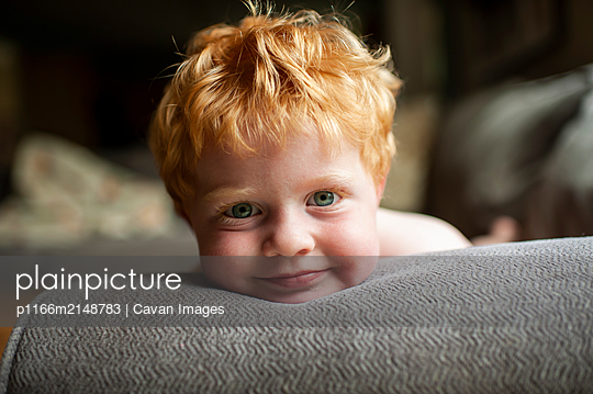 Portrait of toddler boy with red hair laying on couch smiling at home - p1166m2148783 by Cavan Images