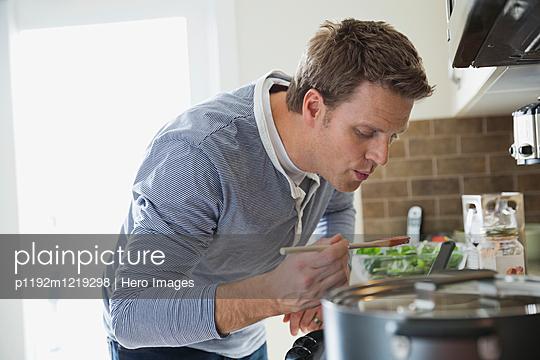 Mid adult man taste testing sauce in domestic kitchen