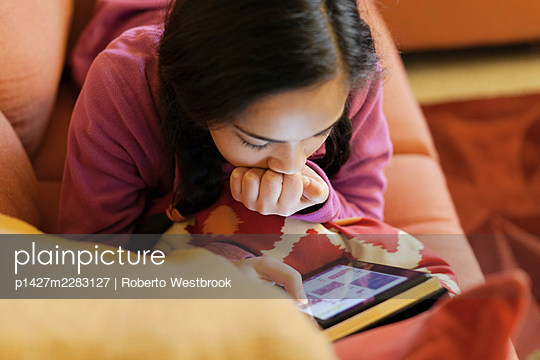 Teenage girl with electronic book - p1427m2283127 by Roberto Westbrook