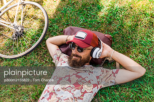 Mature man with red basecap, sunglasses and white headphones - p300m2155822 by Tom Chance