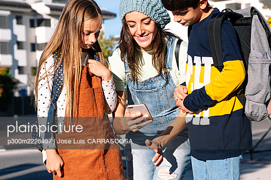 Mother using smart phone standing with kids in public park on sunny day - p300m2226497 by Jose Luis CARRASCOSA