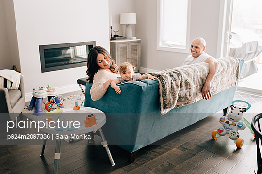 Mother and father reclining on sofa with baby daughter - p924m2097336 by Sara Monika