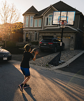 Full length of boy playing basketball on road by house - p1166m2011790 by Cavan Images