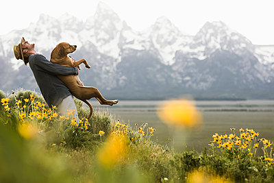 Side view of happy man carrying dog while standing amidst plants by lake against snowcapped mountain - p1166m2034338 by Cavan Images