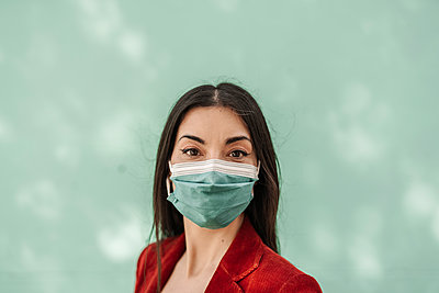 Businesswoman with protective face mask against turquoise wall during COVID-19 - p300m2265913 by COROIMAGE