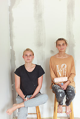 Teenage girls painting wall - p312m1521876 by Christina Strehlow
