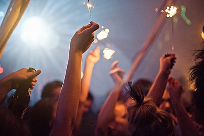Festival crowds with arms raised in holding sparklers and beer bottles at night - p429m1054139 by Philipp Nemenz