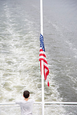 Rear View of Young Boy on Ferry with American Flag - p694m2218914 by Kathryn Sheldon photography