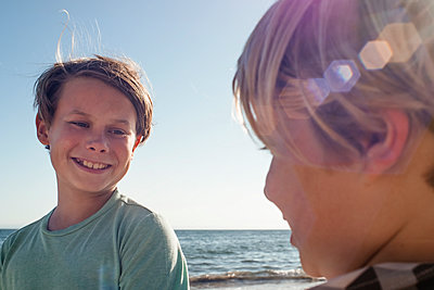Head and shoulders portrait of two smiling boys standing by the ocean. - p924m2208568 by JFCreatives