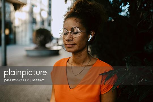 Female entrepreneur listening music through wireless earphones on footpath - p426m2239003 by Maskot