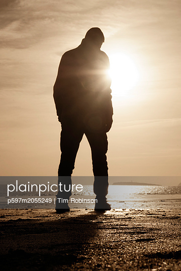 Rearview man standing on beach at low tide - p597m2055249 by Tim Robinson