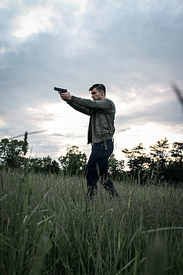 Man with pistol in a field - p1019m1424628 by Stephen Carroll
