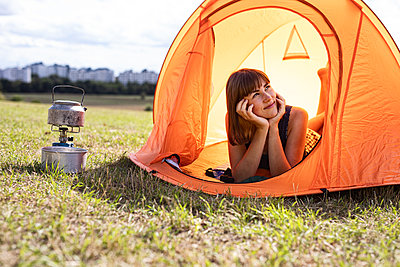 Young woman camps out in the meadow, city in background - p294m2207522 by Paolo
