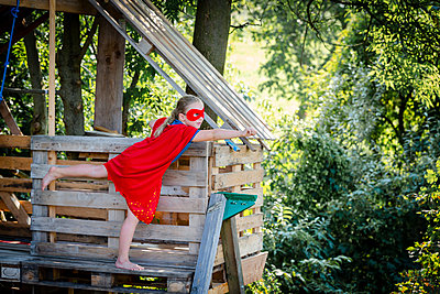 Superhero girl playing in a tree house - p300m2140494 von Epiximages