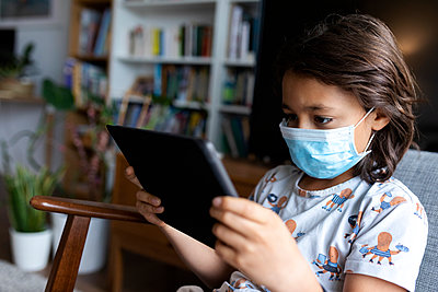 Boy with surgical mask using digital tablet at home - p300m2189189 by Valentina Barreto