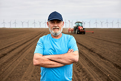 Bearded male farmer with arms crossed standing on plowed agricultural field - p300m2282758 by Zeljko Dangubic