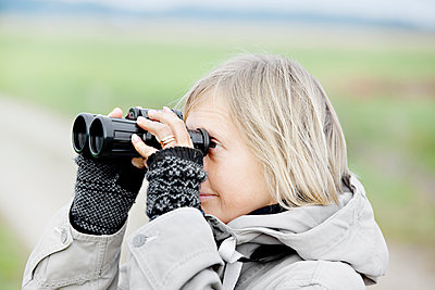 Side view of blonde woman holding binoculars - p312m1551970 by Johner Images