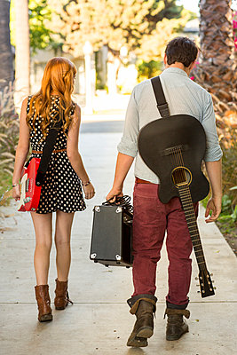 Young couple walking along street carrying guitars and amplifier - p429m898397 by Lauren Devon