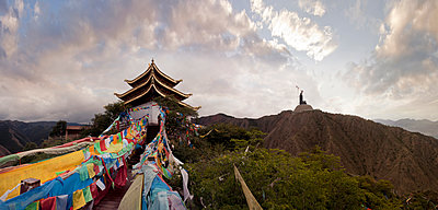 Panoramic view of prayer flags and traditional building on mountain - p555m1306344 by Christopher Winton-Stahle