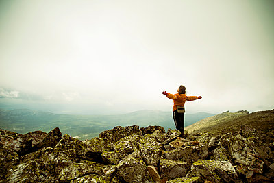 Caucasian hiker with arms outstretched on rocky hilltop - p555m1414517 by Aleksander Rubtsov