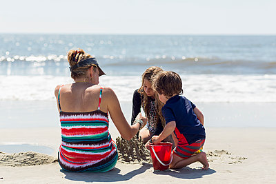 Caucasian family building sand castle at beach - p555m1522754 by Marc Romanelli