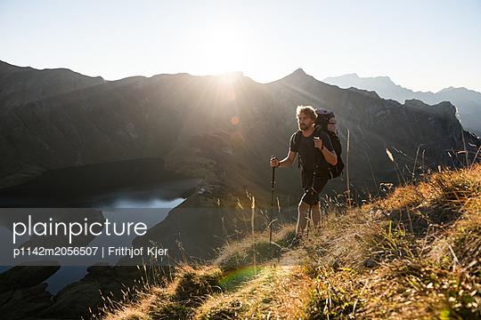 Junger Wanderer vor Bergseekulisse - p1142m2056507 von Runar Lind