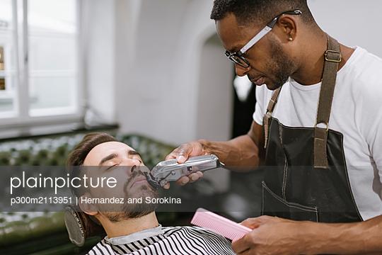 Barber cutting beard of a customer in barber shop - p300m2113951 by Hernandez and Sorokina