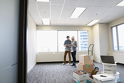 Business people with digital tablet working behind cardboard boxes in new office - p1192m1403487 by Hero Images