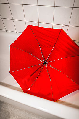 Red umbrella in bathtub - p1418m1571675 by Jan Håkan Dahlström