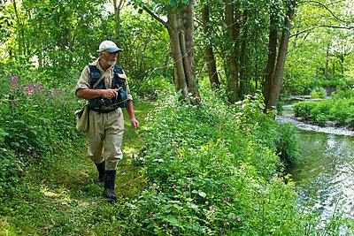 Fisherman walking along river - p42914151f by Ross Woodhall