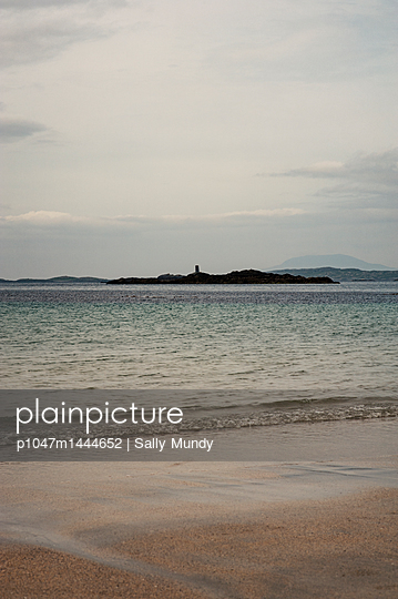 View of distant island from sandy beach - p1047m1444652 by Sally Mundy