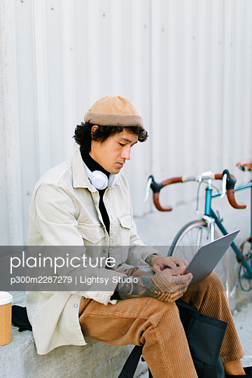 Businessman using laptop by wall - p300m2287279 by Lightsy Studio