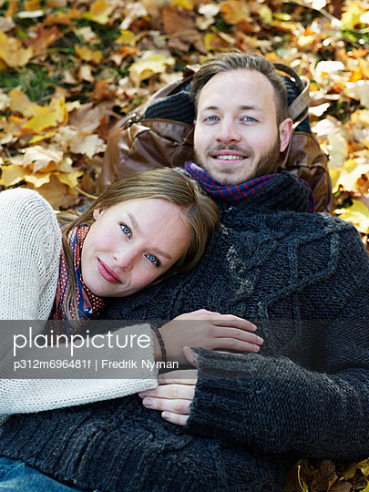 Portrait of young couple lying in leaves - p312m696481f by Fredrik Nyman