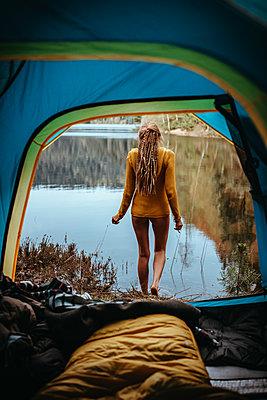 Frau steht vor ruhigem Bergsee - p1455m2203738 von Ingmar Wein