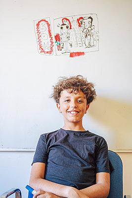 Portrait of smiling boy sitting in front of drawing on a whiteboard - p300m2140243 von Javier De La Torre Sebastian