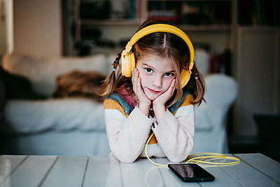 Girl wearing headphones leaning on table with head in hands at home - p300m2225561 by Eva Blanco