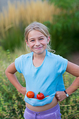Caucasian girl carrying tomatoes in shirt - p555m1410683 by Marc Romanelli
