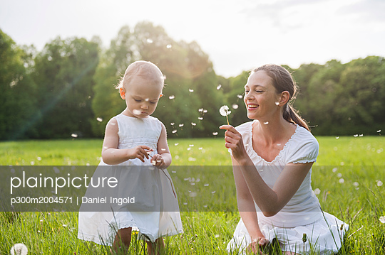 Mother and daughter with blowballs on meadow in summer - p300m2004571 von Daniel Ingold