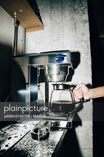 Cropped hand of businessman making coffee at workplace - p426m2194700 by Maskot