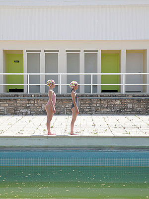Two girlfriends stand along the poolside - p1105m2082556 by Virginie Plauchut