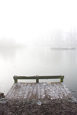 Icy, fishing platform by a lake in winter. - p1121m1111517 by Gail Symes