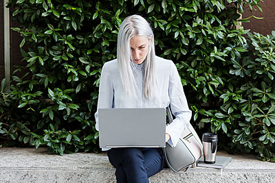 Young businesswoman sitting on a wall in the city using laptop - p300m1505281 by Giorgio Fochesato