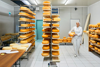 Cheese factory, blurred female worker with cheese wheel in storeroom - p300m2199647 by Zeljko Dangubic