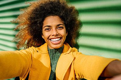 Beautiful Afro woman taking selfie against green wall - p300m2265119 by Ezequiel Giménez
