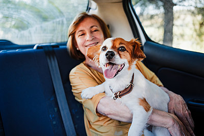 Senior woman with dog sitting in car - p300m2293400 by Eva Blanco