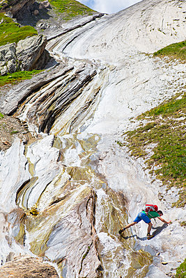 A hiker is scrambling on a spectacular rock formation near the Col des Fours above la Ville des Glaciers.  - p343m1475696 by Menno Boermans