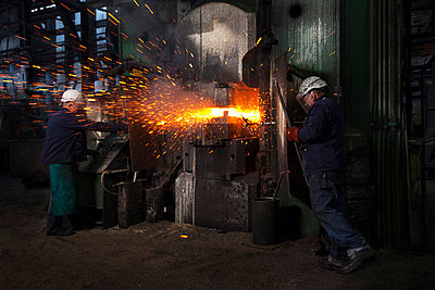Sparks fly as counterblow hammer forms flight bar, the counterblow hammer forges by striking from both above and below mining component - p429m875667f by Charlie Fawell